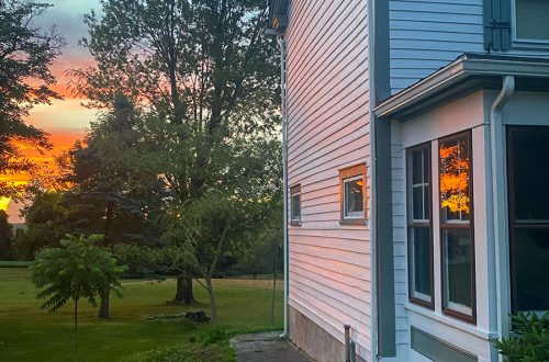 sunset window reflection on colonial farmhouse on the happy list