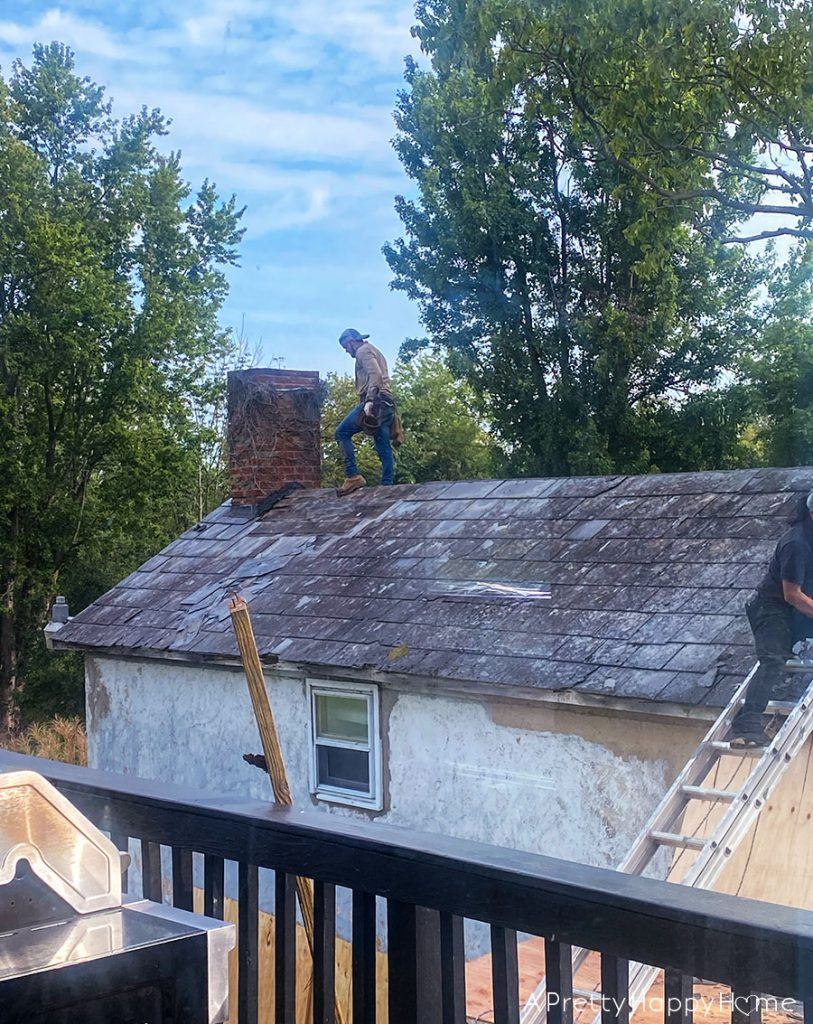 removing a slate roof to install black metal roof carriage house